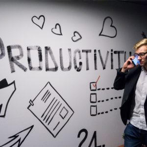 Operations consultant walking past wall that says 'productivity'