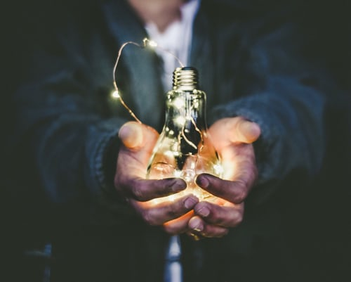 Lightbulb in hands symbolizes creativity