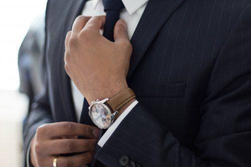 Man straightening his tie.