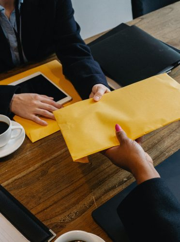 Operations consultant handing over an envelope.