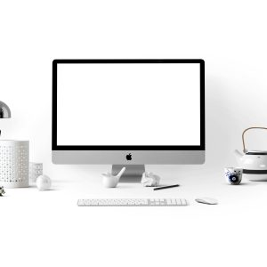 Mac book, home office, lamp, tea kettle, keyboard, and pens.
